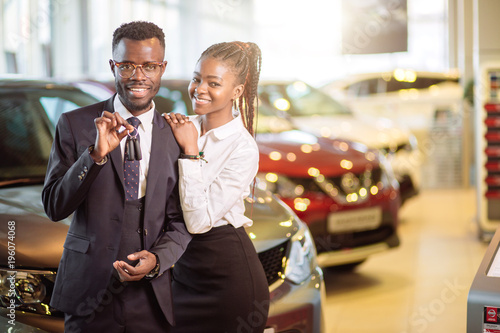 Visiting car dealership. Beautiful african couple is holding a key of their new car, looking at camera and smiling