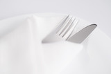 Fork and knife into white napkin on white plate - 196074430