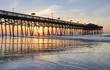 Early morning at the atlantic ocean beach. Beautiful marine landscape with sun rising over calm atlantic ocean beach with wooden pier. South Carolina, Myrtle Beach area, USA. Vacation background.
