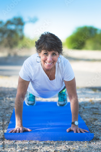 Fit Happy Smiling Woman Exercising on Yoga Mat Outside in Nature