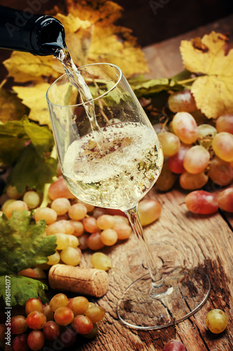 Fototapeta White wine being poured into a glass, vintage wood background, selective focus