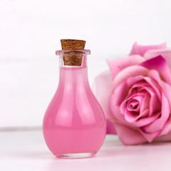 rose essential oil bottle blurred rose flower white background square © dvulikaia