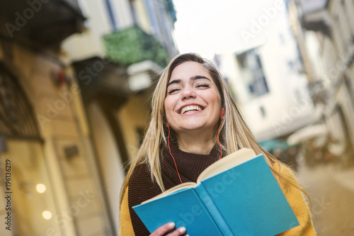 Poster Smiling girl holding a book