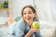 Portrait of a young and cute woman lying with green apple in the cozy and bright bedroom at home