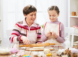 Mother and daughter cooking at home, making the dough for buns - 196143659