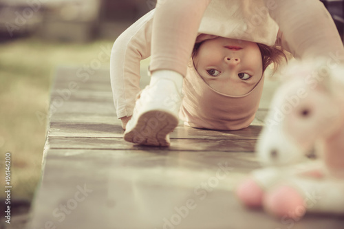 Girl stand on head on sunny day outdoor