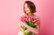 portrait of beautiful woman with bouquet of spring tulips isolated on pink