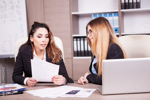 Foto Murales Two women sitting at the office and talking