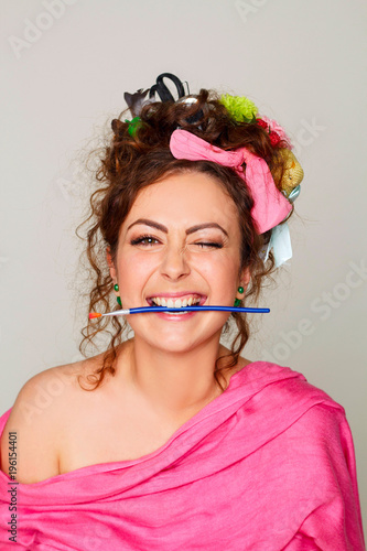 Foto op Plexiglas Kapsalon Portrait of young woman artist with paintbrush in her mouth wearing interesting and creative hairstyle
