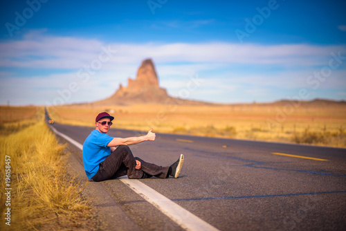Staande foto Arizona Tired hitch-hiker sitting on a road