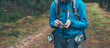Young male backpacker with smartphone on forest path.
