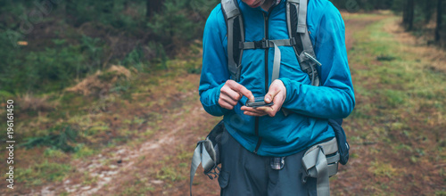 Fotobehang Natuur Young male backpacker with smartphone on forest path.