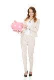 Business woman with a piggybank. - 196163826