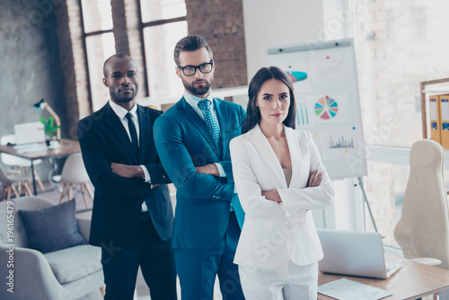 Stylish modern business trio sharks in tux, tuxedo with tie, having arms crossed, standing in work place, station, looking at camera, men with stubble and glasses and beautiful woman