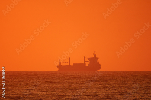 Papiers peints Morning Glory Silhouette of ship on the ocean at sunrise