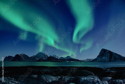 Northern Lights, Aurora Borealis shining green in night starry sky at winter Lofoten Islands, Norway