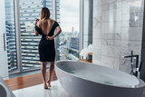 Back view of young woman wearing white bathrobe standing in bathroom looking out the window with bathtub in foreground - 196180877