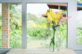 Yellow lilies placed at the side of the window