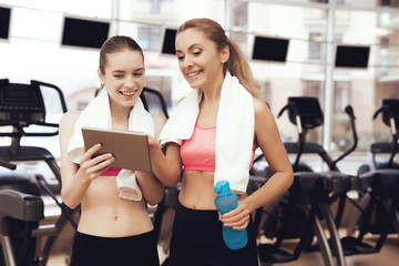 Mother and daughter using tablet at the gym. They look happy, fashionable and fit. © freeograph
