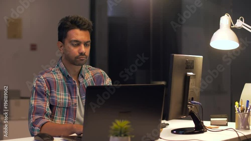 creative man with computer working at night office