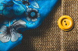 Blue scarf with flower pattern and yellow button on brown textile background