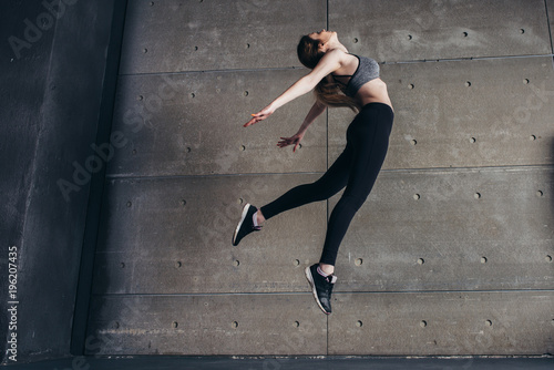 Wall mural Sports young woman doing back bend jump