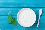 Fresh greek yogurt in bowl on blue vintage table top view. - 196211094