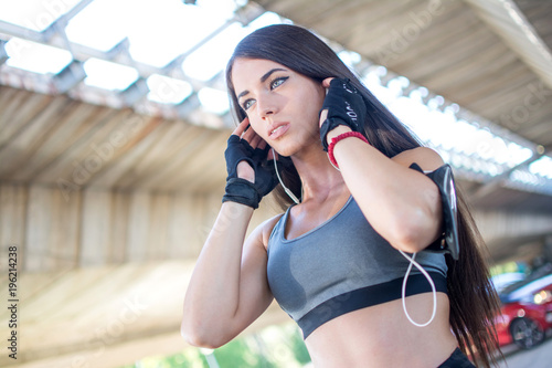 Fototapeta Portrait of young fit woman in sportswear with earphones listening to music outdoors.