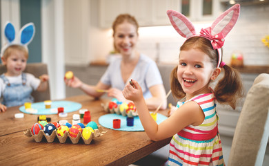 Happy easter! family mother and children paint eggs for   holiday.