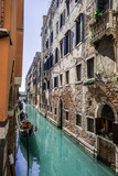 Narrow side canal with boats in Venice, Symbol of Venice, Venetian transport boats, Classical street in Venice