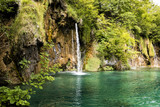 Paradise landscape with waterfall flowing into a pond in Plitvice Lakes National Park in summer in Croatia