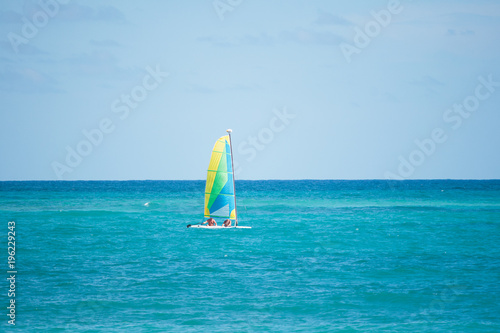 Fotobehang Zeilen boat with bright sails on the waves of the blue sea. Dominican Republic