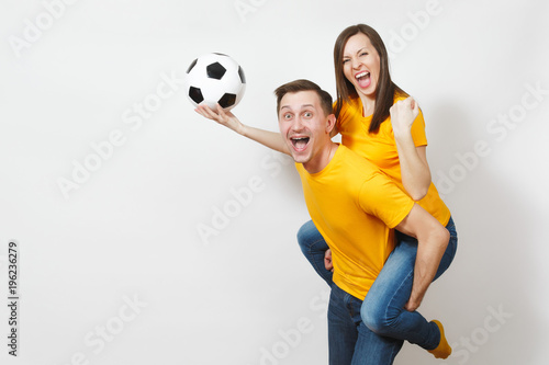 Fototapeta Inspired young couple, woman sit on man piggyback, fans with soccer ball cheering favorite football team expressive gesticulating hands isolated on white background. Family leisure, lifestyle concept.