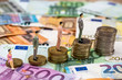 small toys people are on the euro coins and banknotes in euros