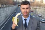 Provocative businessman eating a banana