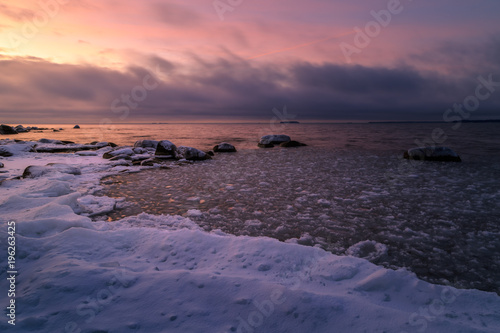 Staande foto Zee zonsondergang snow and ice on rocks on the coast during a beautiful sunset