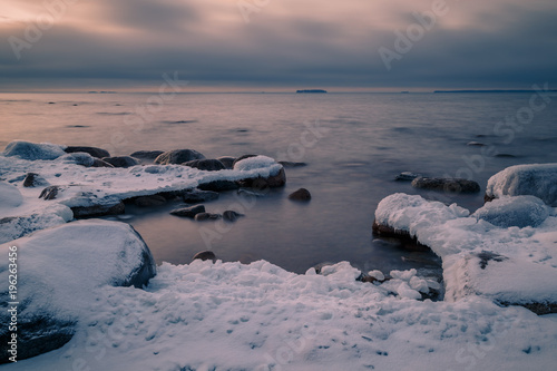 Aluminium Grijs snow and ice on rocks on the coast during a beautiful sunset