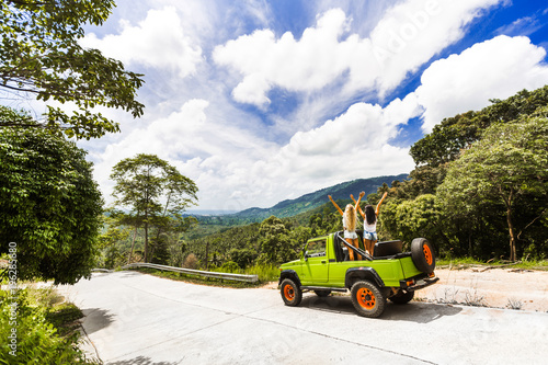 Fototapeta two girls best friends travel on a tropical island in a car with an open top are having fun having a smile. enjoyment travel, excursion summer dressed shorts T-shirts sunglasses, blue sky