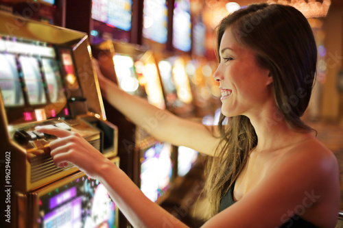 Foto op Plexiglas Las Vegas Asian woman gambling in casino playing on slot machines spending money. Gambler addict to spin machine. Asian girl player, nightlife lifestyle. Las Vegas, USA.