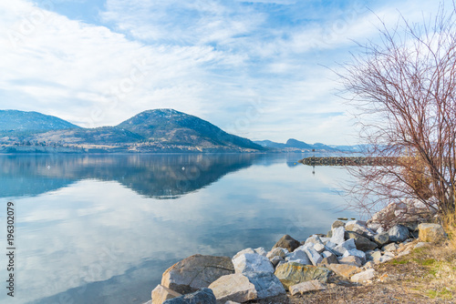 Aluminium Pier Rocky shoreline of breakwater with calm lake reflecting sky and mountains in early spring
