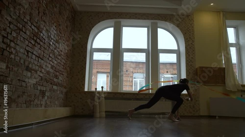 Wall mural sport athletics. gymnast calisthenics ribbon program exercise. young fit girl artistic dance workout in a studio