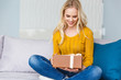 beautiful smiling young woman holding gift box while sitting on sofa at home