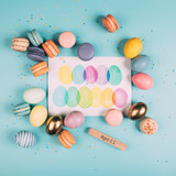 top view of easter eggs and macarons around happy easter greeting card on blue surface - 196320082