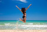 Happy woman in a jump on beach