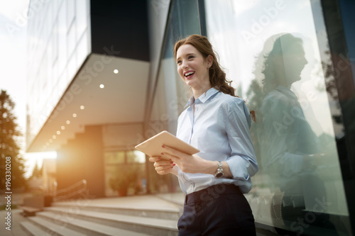 Portrait of pretty student or businesswoman in smart casual using digital tablet