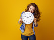 stressed stylish woman against yellow background biting clock