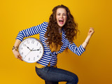cheerful woman on yellow background with clock rejoicing - 196331880