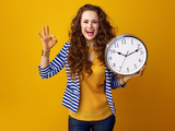 woman isolated on yellow background with clock showing ok