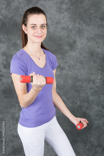 Wall mural Fitness model woman with dumbbells on grey studio background. Young girl in fitwear with sport equipment