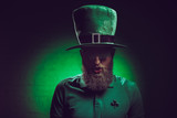 portrait of bearded young man in green irish hat and funny eyeglasses - 196336853